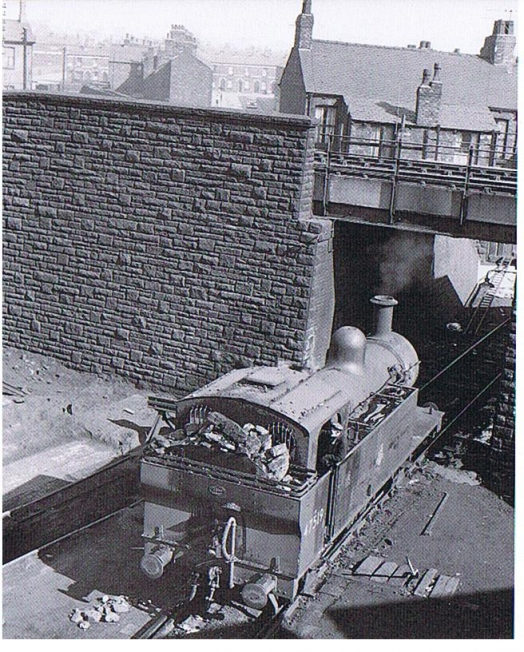 Tank locomotive passing under a bridge